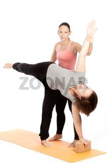 Yoga teacher provides assistance in training, ardha candrasana