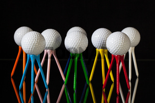 White golf balls and different colored tees