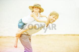 Vater trägt Tochter auf Rücken im Sommer