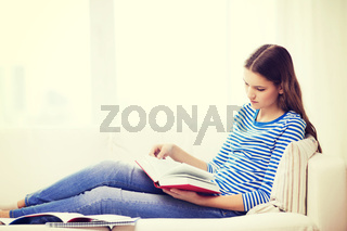 calm teenage girl reading book on couch