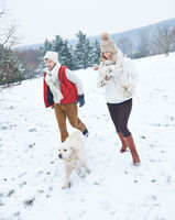 Paar mit Hund geht im Winter spazieren