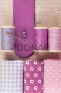 Sewing threads, needle and fabrics on a wooden box