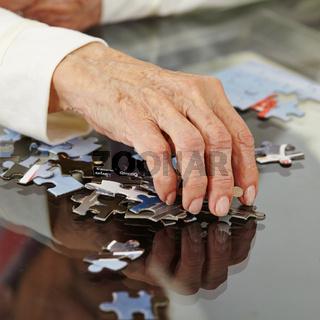 Faltige alte Hand greift nach Puzzlestück