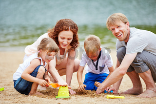 Familie mit Kindern spielt im Sand am Strand
