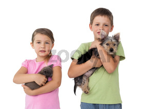 Cute siblings holding their pets and smiling at camera