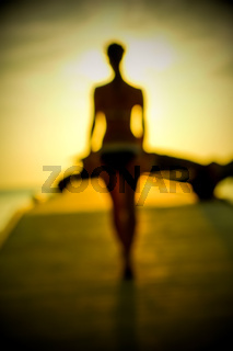 Silhouette of a girl walking along the pier at sunset