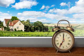 View of house on summer vineyard landscape from window with alarm clock