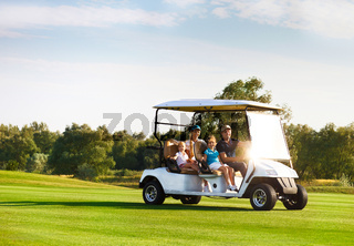 Beautiful family portrait in a cart at the golf course