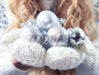 Young blond woman holding silver decorative balls wearing white gloves