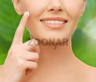 closeup of woman hand applying moisturizing cream