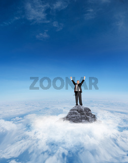 Composite image of mature businessman cheering with arms up
