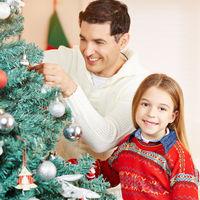 Mann und Mädchen schmücken Weihnachtsbaum zu Weihnachten
