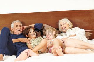 Großeltern kitzeln Enkel auf Bett