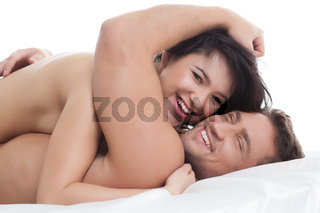 Happy naked lovers embracing lying in bed