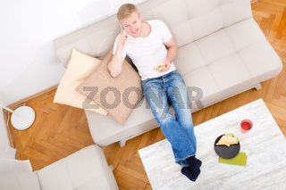 Young man with a Sandwich on the Sofa