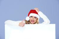 Happy Woman in Santa Hat Behind Big Board
