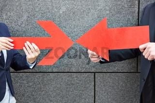 Zwei Leute zeigen mit roten Pfeilen aufeinander