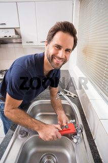 Man fixing tap with tool