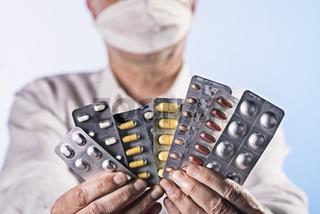 Arzt hält Blister mit Medikamenten in den Händen
