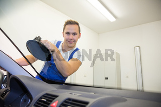 Glazier replaces windshield or windscreen on a car in garage