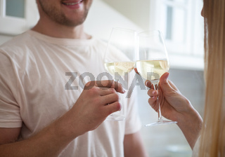 Happy young couple enjoying a glass of white wine