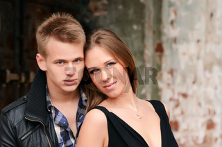 Young enamoured pair a brick wall