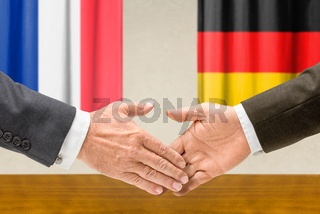 Representatives of  France and Germany shake hands