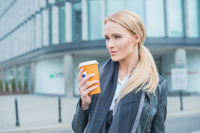 Attractive blond woman standing drinking coffee
