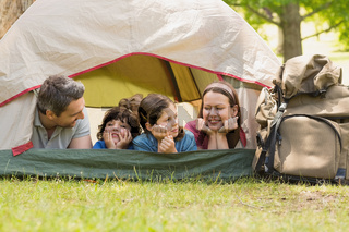 Couple with kids lying in the tent at park