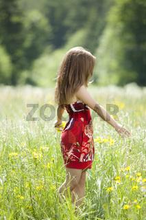 Vertraeumtes Maedchen in einer Blumenwiese