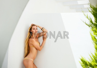 Sexy young blond woman posing in a golden bikini