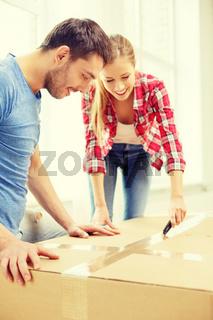 smiling couple opening big cardboard box