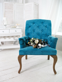 Wedding bouquet with ranunculus on the blue armchair