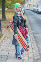 Trendy young woman carrying a skate board