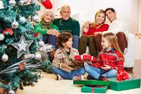 Mädchen gibt Geschenk an Bruder zu Weihnachten