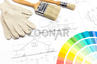 Brushes gloves and color samples over house plan on background
