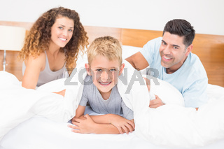Cute young family smiling at camera on bed