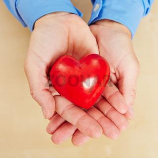 Mann hält rotes Herz in seinen Händen