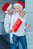Husband surprising his wife with a Christmas gift
