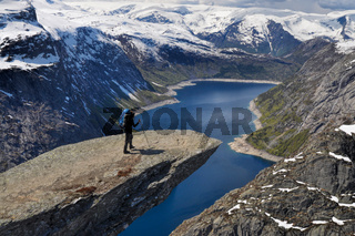 Hiker walking to the edge of Trolltunga rock
