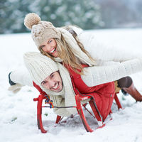 Paar hat Spaß beim Rodeln im Winter
