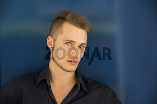 Handsome blond young man against metal blue wall