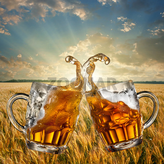 Splash of beer against wheat and sunset