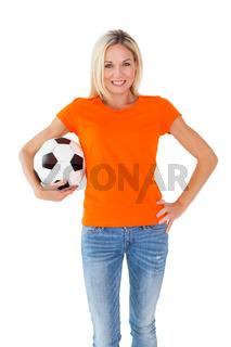 Football fan holding ball in orange tshirt