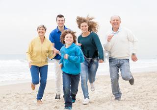 Happy family jogging atthe beach