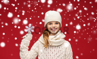 smiling girl in winter clothes with big snowflake