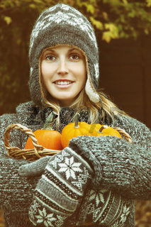 Young woman holding a basket of pumpkins