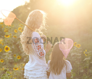 Cheerful mother and her daughter in summer evening