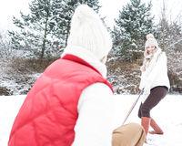 Frau zieht Mann auf Schlitten im Schnee