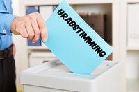 Hand mit Stimmzettel für Urabstimmung